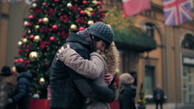 couple hugging in front of a Christmas tree