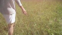 woman walking through tall grass