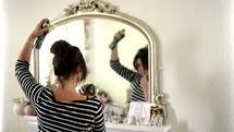 woman getting ready in a mirror