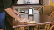 waiter cleaning a table at a restaurant