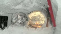 Cleaning snow off the headlight of a car.