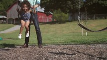 father pushing his daughter on a swing