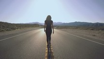 a woman walking in the middle of a road