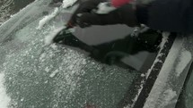 Scraping ice off o car windshield.