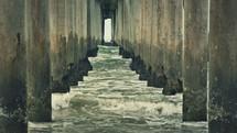 Ocean waves moving under pier legs.