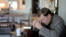 Man praying and reading the Bible.