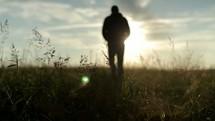 man walking in a field at daybreak