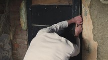 a man trying to pry a door open