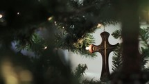 Cross ornament on a Christmas tree.