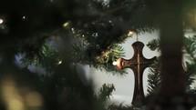 Cross ornament on a Christmas tree.