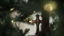 Hanging a cross ornament on a Christmas tree