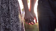 Couple holding hands outdoors at sunset.