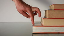 fingers walking up a stack of books