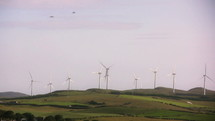 Moving wind turbines on grassy hills.