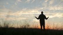 Silhouette of a man worshipping in reverence outside.