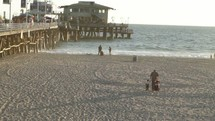 Families on the beach near a busy pier.