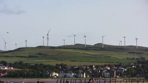 Moving wind turbines on a grassy hill over a town.