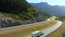 RV travelling on a highway through the mountains.
