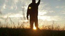 Silhouette of man in a field at sunrise jumping for joy.