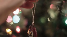 hanging an ornament on a Christmas tree