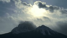 Timelapse of clouds rolling across a mountaintop.