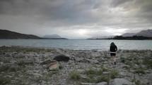 girl walking on a mountain lake shore landscape