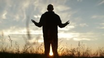 Silhouette of a reverent man praising God outside.