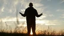 Silhouette of a reverent man praising God outside.