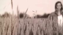 woman walking through a field of wheat