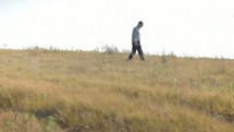 Man with a Bible walking through a field.
