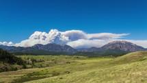 Billowing smoke cloud from behind a mountain range.