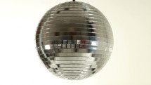 a spinning mirror ball against white background