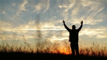 Silhouette of a man with lifted hands in worship outside.