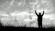 silhouette of a man praising God in a field