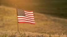 2 shots of an American flag in the grass waving in the breeze