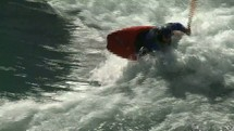 Person in canoe paddling on roaring rapids.