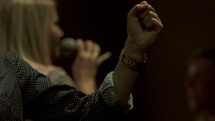 a woman singing into a microphone leading a worship service in song