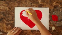 artist painting a red heart