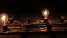 Light fixture with illuminated bulbs and broken bulbs.