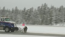Snow plow truck on a highway in the winter.