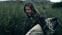 Man in a camouflage jacket with a surfboard