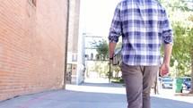 man walking down a street carrying his Bible