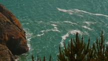 Ocean waves near a rocky cliff and trees.