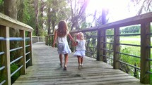 sisters running holding hands on a boardwalk