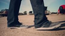 feet of a man walking through a junk yard