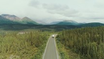 aerial view over a camper traveling down a road