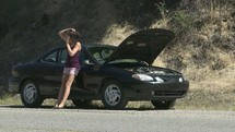 broken down vehicle and a young woman on a cellphone