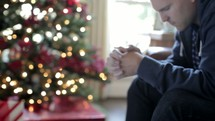 man reading a Bible by a Christmas tree