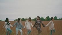 women walking through a field of tall grasses