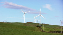 Moving wind turbines on a grassy hill.